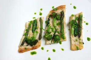 Kartoffelpizza mit Mandelguss und grünem Spargel, in Stücke geschnitten